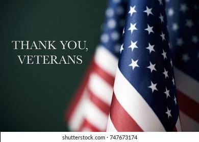 enkele Amerikaanse vlaggen en de tekst dank u veteranen tegen een donkergroene achtergrond
