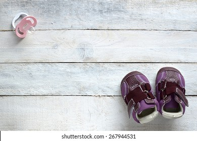 Some baby stuff on a white wood, top view. A a pacifier and lilac shoes.
