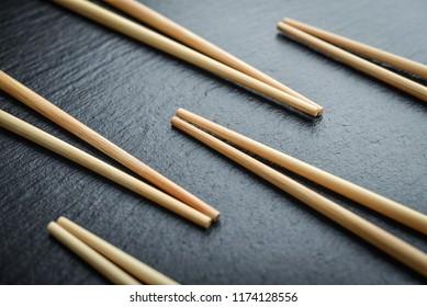 Some bamboo chopsticks on black slate background