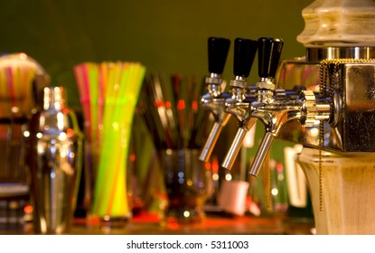 Some beer taps in a cocktail bar, focus on the first tap, background