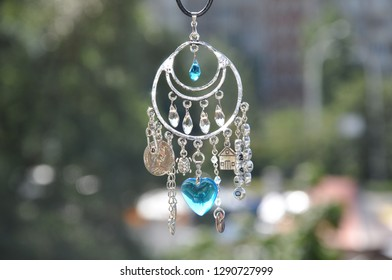 Some believe in luck. Name amulet for good luck. Luck amulet hung out outdoor. Silver amulet with gems and pendants. Believing in magic protecting the holder of amulet. Jewelry charm or talisman.