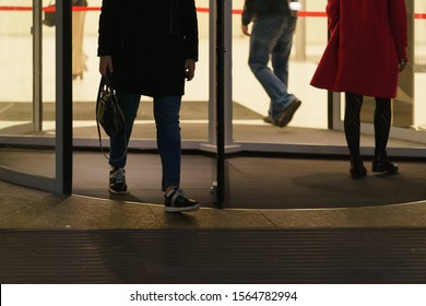 Some bisnesspersons leaving the office building, some coming. Revolving door and men' and women' feet photography. Urban office lifestyles in the end of day.