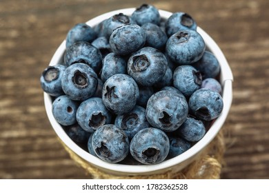 Some blueberries in a decorate small bucket on wooden banch in the garden on summer sunset, close up shot, healthy food concept