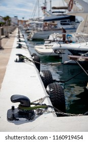 Some boats moored to black bollards in a marina on an island in the Mediterranean Sea