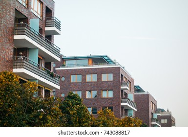 some brick apartment houses with green bushes