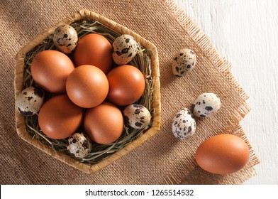 Some brown chicken eggs and several small motley quail eggs on straw in wicker basket and three quail eggs and one chicken egg on sackcloth. All this on white wooden table.