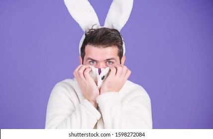 Some bunny loves you. Man wearing rabbit ears. Easter hare. Bearded man in easter rabbit costume. Happy Hipster dressed for Easter party. Celebrating spring, new life and fertility. Spring holiday.
