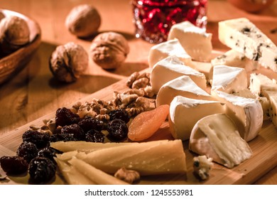 Some cheeses and raisins, nuts and pomegranates juce in the glass on the wooden plate