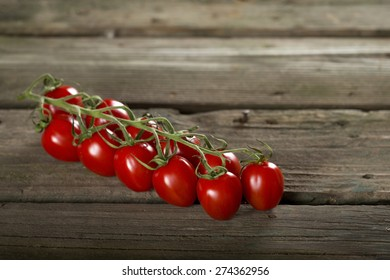 Some cherry tomatoes on a wooden surface