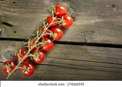 Some cherry tomatoes on a wooden surface with copy space
