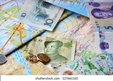 Some Chinese bank notes and coins on a Chinese maps