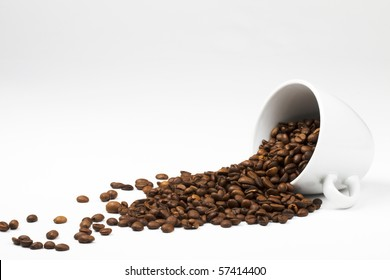 some coffee beans falling from a coffee cup on white background