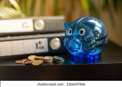 Some coins, coins and a blue piggy bank