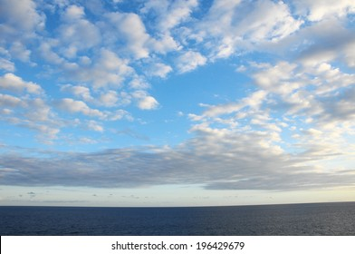 Some Colored Clouds over the Ocean on a Blue Sky