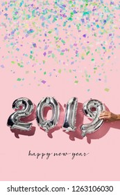 some confetti, a man forming the number 2019, as the new year, with some silvery number-shaped balloons and the text happy new year on a pink background