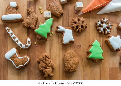 Some of the cookies covered with icing. Other cookies prepared for decoration. Wooden background and cones with icing