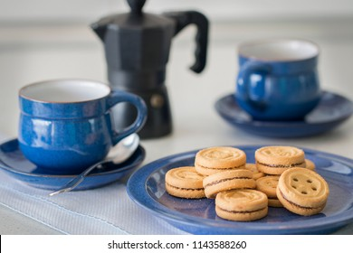 Some cookies on a blue plate. Background: two cups and a moka.