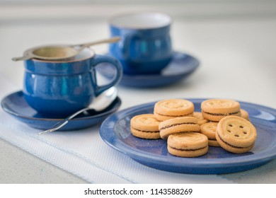 Some cookies on a blue plate. Background: two cups.