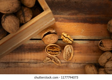 Some cracked fresh harvested walnuts on wooden table or floor