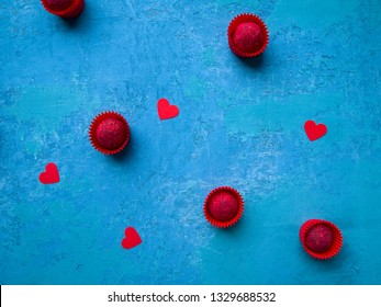 Some crimson chocolate truffles with   sublimated raspberries in red candy wrapper and red hearts on a blue concrete background. Love concept, valentine card.