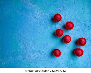 Some delicious chocolate truffles covered with raspberry sprinkle on a blue concrete background. Tasty and colorful dessert.