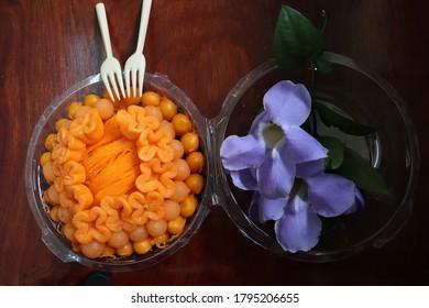 Some delicious Thai desserts in a plastic box. They are Tong Yip (Flower egg yolk tart), Tong Yord (Round egg yolk tart), Med Kanun (Mung bean yolk) and Foi tong (Shredded egg yolk tart)
