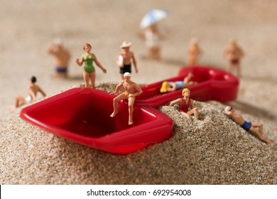 some different miniature people wearing swimsuit relaxing next to a red toy shovel on the sand of the beach
