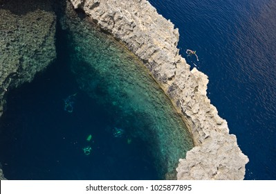 Some divers and a snorkeler are examining an underwater stone arch known as blue hole near the Azure Window on Gozo, Malta.
