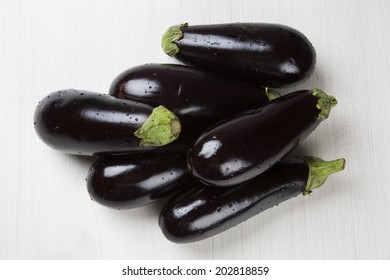 Some eggplants over a white wooden surface