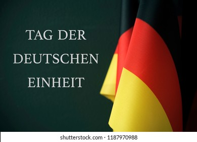 some flags of Germany and the text Tag der Deutschen Einheit, Day of German Unity written in German, against a dark green background