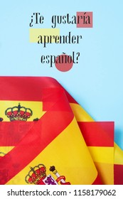 some flags of Spain and the question te gustaria aprender espanol? would you like to learn Spanish? written in Spanish, on a blue background