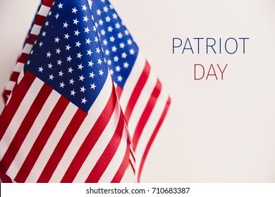 some flags of the United States and the text patriot day against an off-white background