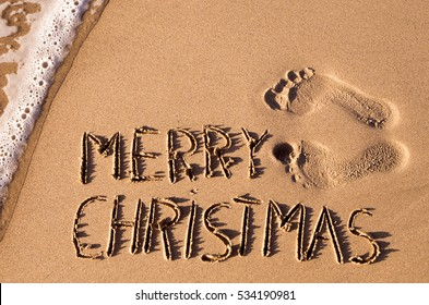 some foot prints and the text merry christmas written in the sand of a beach