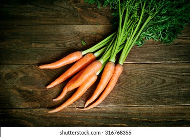 Some fresh carrots at the wooden table