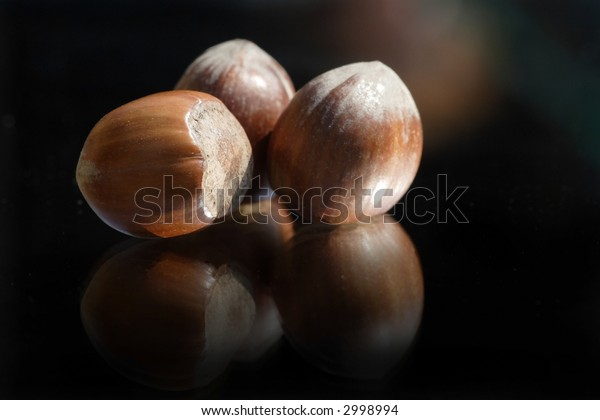 some fresh hazelnuts on a reflecting surface