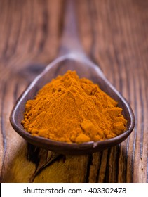 Some fresh Turmeric on an old wooden table (detailed close-up shot, selective focus)