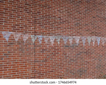 some garlands drawn with colored chalk on a red brick wall