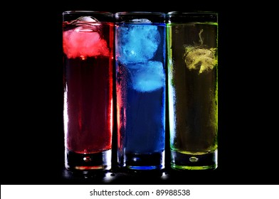 some glasses with cocktails of different colors on a black background