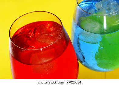 some glasses with cocktails of different colors