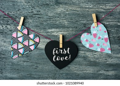 some hearts hung with clothespins in a clothes line and a black heart-shaped signboard with the text first love written in it, against a gray rustic wooden background