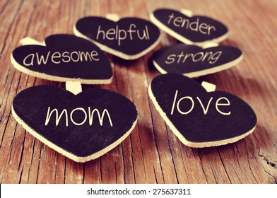 some heart-shaped blackboards with concepts referring to a good mom written in them, such as love, helpful, awesome, tender or strong, placed on a rustic wooden surface