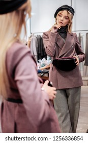Some hesitations. Elegant appealing woman hesitating about buying waist bag in her favorite concept store