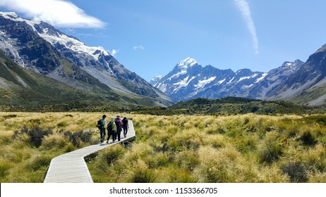 Some hikers visiting the beautiful Hooker Valley. This breathtaking place is located in Aoraki, New Zealand. It is a famous tourist attraction. Visitors can enjoy alpine streams, glacier and lake.