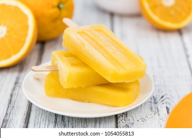 Some homemade orange popsicles (selective focus) on a vintage background