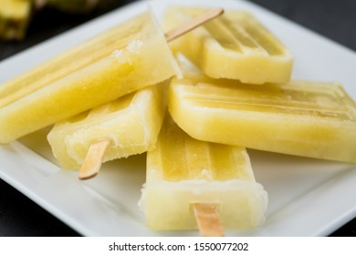Some homemade Pineapple Popsicles (selective focus) on a rustic background