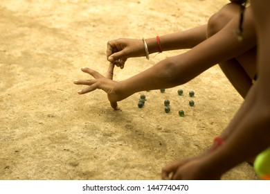 Some Indian little kids are playing marble on the road with their friends on a sunny day