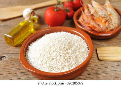 some ingredients to prepare a spanish paella or arroz negro, such as rice, tomato, garlic or shrimps, on a rustic wooden table
