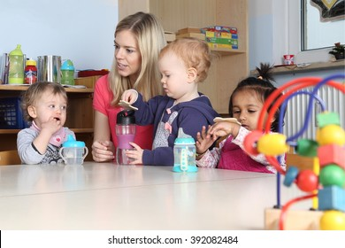 Some Kindergarten or nursery kids on a table drinking and playing