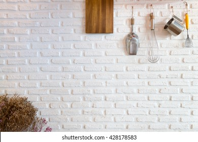 Some kitchenware hang on white brick wall : use for background