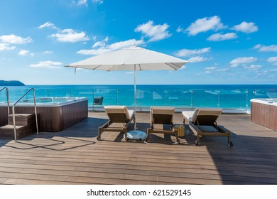 Some lounges at the deck at the ocean beach  of luxury caribbean, tropical resort.